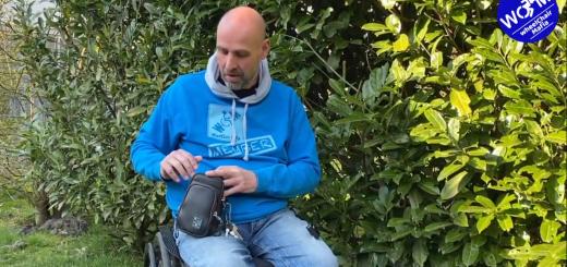 Muž na vozíku držiaci malú tašku
